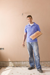 Male plasterer holding towel near plastered wall