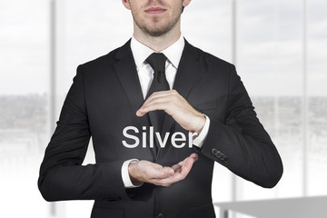 businessman protecting word silver with hands