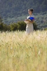 Businesswoman with paperwork in rural field