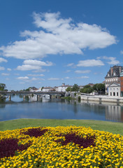 View of town and bridge spanning river on sunny day, Jarnac and the Charente river, West Central France