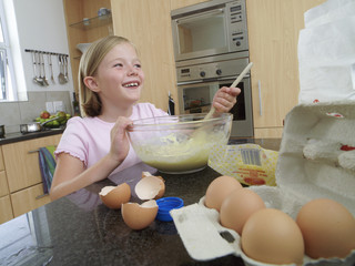 Girl (6-8) standing in kitchen, mixing flour, eggs and milk in bowl with wooden spoon, laughing