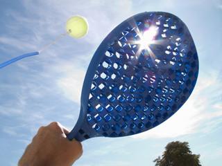 Sun shining behind paddle hitting tennis ball