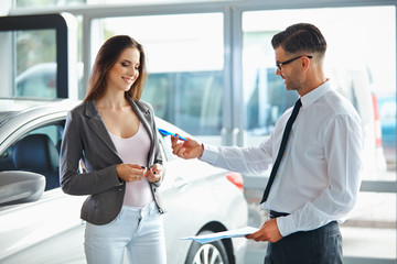 Young Woman Signing Documents at Car Dealership with Salesman