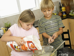 Boy (5-7) and girl (6-8) making cake mix in kitchen, girl pouring flour into glass bowl (tilt)
