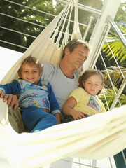 Father and children (5-8) relaxing in hammock on balcony, smiling, man sleeping, portrait (tilt)