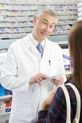 Pharmacist explaining medication to customer in pharmacy