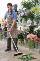 Male florist in apron standing in flower shop, sweeping floor with broom, smiling, portrait