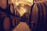 Wooden barrels with wine in a wine vault, Italy poster