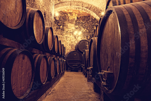 Poster Wijn Wooden barrels with wine in a wine vault, Italy