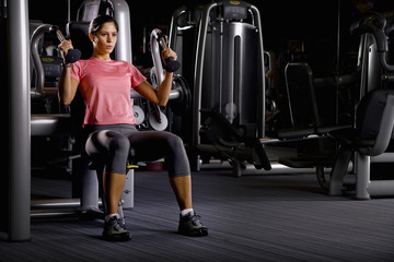 Woman weight lifting with exercise equipment in health club