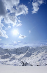 View of snowy mountain range and sun in blue sky