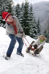 Man pulling girlfriend on sled on remote snowy hillside