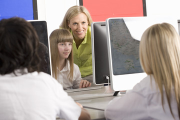 Teacher helping students working on computers in school computer lab