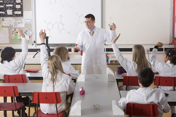 Students answering chemistry teacher's questions in classroom