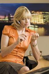 Blonde receptionist in orange short-sleeved blouse sitting on reception desk, filing nails