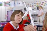 Fototapety Serious school girl looking at model wind turbine in classroom