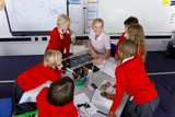 Fototapety Teacher and school children looking at solar panel and model wind turbines