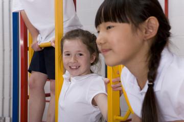 School children climbing gymnasium climbing equipment