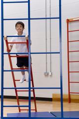 School boy climbing up gymnasium climbing equipment