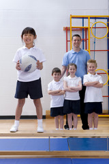 School girl standing on bench and holding ball in school gymnasium with teacher and classmates watching