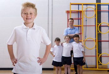 School boy standing in gymnasium with teacher and classmates watching
