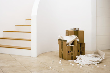 Small stack of boxes, paper and packing foam beside staircase in sparse room