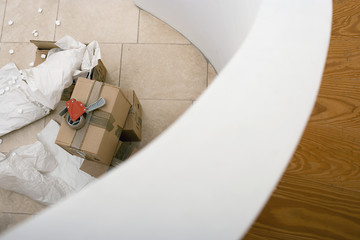 Tape duct dispenser on top of sealed cardboard box, paper and packing foam on floor beside staircase