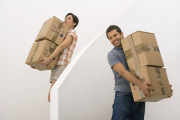 Couple moving house, woman carrying small stack of boxes down staircase, man waiting, smiling
