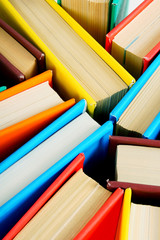 Multi-coloured books from above. Close up.