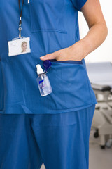 Nurse with hand sanitizer bottle attached to her pocket