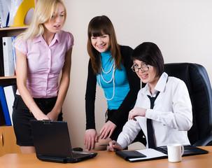 Three pretty businesswomen communicate in office