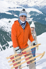 Couple standing in hillside together holding sled