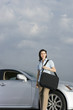 Businesswoman standing beside car, carrying shoulder bag, smiling, portrait