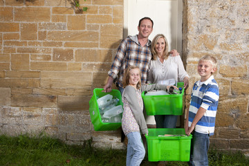 Smiling family holding bins full of recycling materials