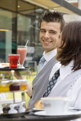 Two young waiters working at pavement cafe, carrying trays of beverages, smiling, close-up