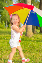 little fun girl walks in the Park with colorful umbrella