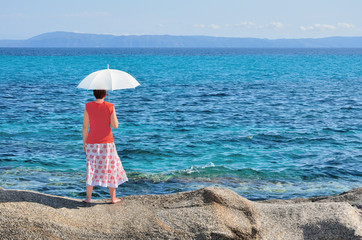 Woman with umbrella standing on the rock near the sea