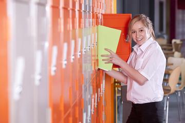 Student removing binder from school locker