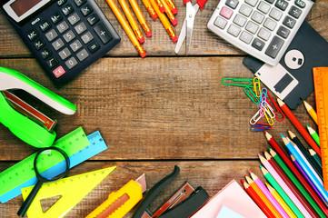 Back to school. School tools around. Wooden background.