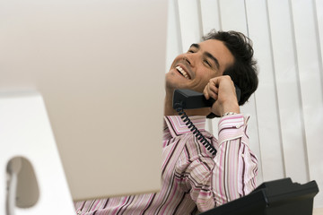 Businessman sitting at desk in office, using telephone, laughing, head back, focus on background