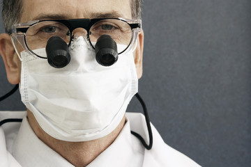 Male dentist wearing surgical mask and surgical loupes, close-up, front view, portrait