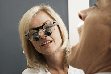Female dentist wearing surgical loupes, examining patient, close-up (differential focus)