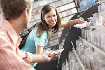 Young man passing CD to woman in record shop, bending down, smiling, side view, focus on background (tilt)