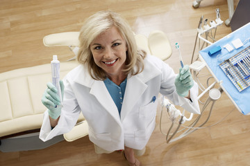 Female dentist holding toothpaste and toothbrush in dental surgery, smiling, portrait, overhead view