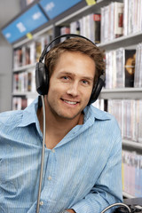 Young man wearing headphones, listening to CDs in record shop, smiling, close-up, portrait
