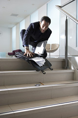 Businessman dropping briefcase on steps in office lobby, contents spilling onto floor, low angle
