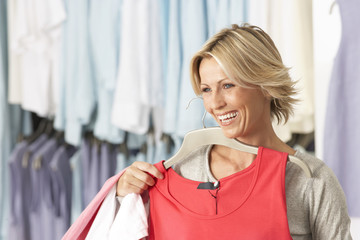 Mature blonde woman shopping in clothes shop, holding red vest top on coathanger, smiling