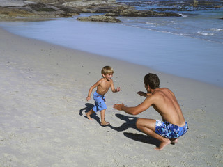 Father and son (4-6) playing on beach, boy running into man's arms, smiling, elevated view