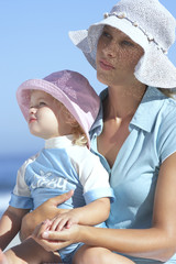 Mother and daughter (2-4) in sun hats sitting on beach, girl in woman's lap, close-up