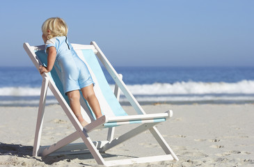 Girl (2-4) standing on deckchair on sandy beach, rear view, sea in background